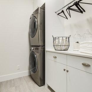 Immagine di una sala lavanderia contemporanea di medie dimensioni con ante lisce, ante bianche, top in superficie solida, pareti bianche, pavimento in gres porcellanato, lavatrice e asciugatrice a colonna, pavimento grigio e top bianco