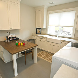 Inspiration for a mid-sized transitional utility room in Portland with a farmhouse sink, shaker cabinets, white cabinets, tile benchtops, beige walls, ceramic floors, a side-by-side washer and dryer and grey floor.
