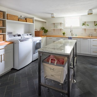 Photo of a large transitional l-shaped dedicated laundry room in Chicago with a drop-in sink, shaker cabinets, white cabinets, wood benchtops, white walls, slate floors, a side-by-side washer and dryer, grey floor and brown benchtop.