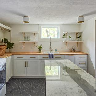 Bild på en stor vintage bruna l-formad brunt tvättstuga enbart för tvätt, med en nedsänkt diskho, skåp i shakerstil, vita skåp, träbänkskiva, vita väggar, skiffergolv, en tvättmaskin och torktumlare bredvid varandra och grått golv