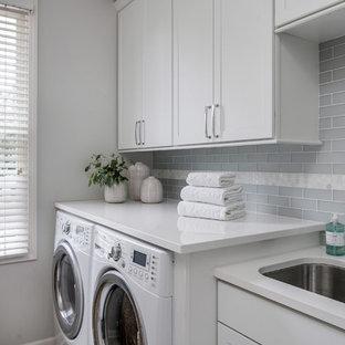 Exempel på en mellanstor klassisk grå linjär grått tvättstuga enbart för tvätt, med en undermonterad diskho, skåp i shakerstil, vita skåp, bänkskiva i kvarts, grå väggar och en tvättmaskin och torktumlare bredvid varandra