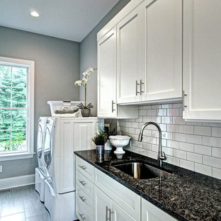 Inspiration for a large classic galley utility room in Philadelphia with a submerged sink, shaker cabinets, white cabinets, granite worktops, grey walls, porcelain flooring, a side by side washer and dryer, grey floors and black worktops.