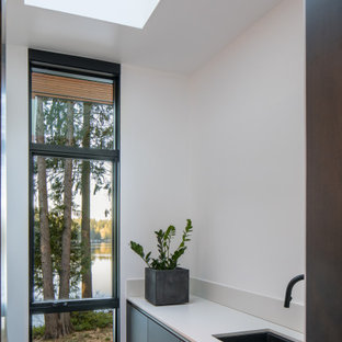 Design ideas for a mid-sized contemporary galley dedicated laundry room in Seattle with an undermount sink, flat-panel cabinets, grey cabinets, quartz benchtops, white splashback, a side-by-side washer and dryer, grey floor and white benchtop.