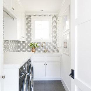 Foto på en maritim vita l-formad tvättstuga enbart för tvätt, med en undermonterad diskho, skåp i shakerstil, vita skåp, flerfärgade väggar, en tvättmaskin och torktumlare bredvid varandra och grått golv