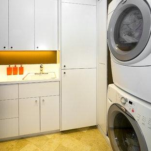 Immagine di una lavanderia minimalista con lavatrice e asciugatrice a colonna, ante bianche e pavimento giallo