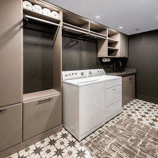 Design ideas for a large classic single-wall separated utility room in DC Metro with a submerged sink, flat-panel cabinets, beige cabinets, engineered stone countertops, black walls, porcelain flooring, a side by side washer and dryer, multi-coloured floors and grey worktops.