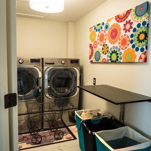 Foto di una sala lavanderia bohémian con ante con riquadro incassato, ante in legno chiaro, top in laminato, pareti beige, pavimento con piastrelle in ceramica e lavatrice e asciugatrice affiancate