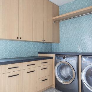 Пример оригинального дизайна: отдельная, угловая прачечная в современном стиле с плоскими фасадами, светлыми деревянными фасадами, синими стенами, со стиральной и сушильной машиной рядом, серым полом и серой столешницей
