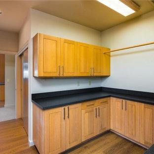 Idee per una sala lavanderia minimal di medie dimensioni con lavello sottopiano, ante in stile shaker, ante arancioni, top in saponaria, pareti bianche, pavimento in legno massello medio, lavatrice e asciugatrice affiancate, pavimento arancione e top nero