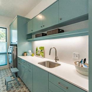 Foto på en stor funkis vita parallell tvättstuga enbart för tvätt, med en undermonterad diskho, släta luckor, turkosa skåp, bänkskiva i kvartsit, vita väggar, en tvättmaskin och torktumlare bredvid varandra och turkost golv