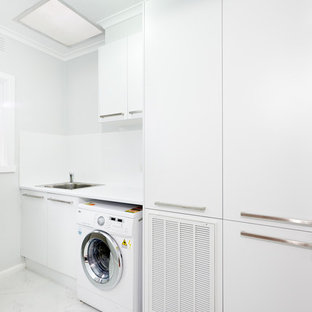 Minimalist single-wall dedicated laundry room photo in Melbourne with a drop-in sink, flat-panel cabinets, white cabinets and white walls