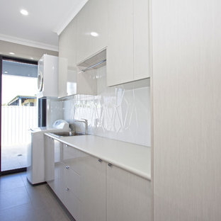 Photo of a mid-sized modern single-wall dedicated laundry room in Other with a single-bowl sink, laminate benchtops, white walls, flat-panel cabinets, white cabinets, white splashback, glass sheet splashback, ceramic floors, a stacked washer and dryer, grey floor and white benchtop.