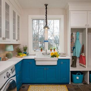 Réalisation d'une buanderie tradition avec un évier de ferme, un placard à porte shaker, des portes de placard bleues, un plan de travail en quartz modifié, un mur beige, un sol en ardoise, des machines côte à côte, un sol marron et un plan de travail blanc.