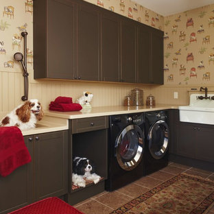 Elegant brown floor laundry room photo in Detroit with a farmhouse sink, shaker cabinets, dark wood cabinets, beige walls and a side-by-side washer/dryer