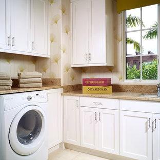 Esempio di una lavanderia tropicale con lavello sottopiano, ante bianche e lavatrice e asciugatrice affiancate