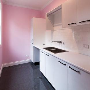 Cette image montre une buanderie minimaliste avec un mur rose et un sol gris.
