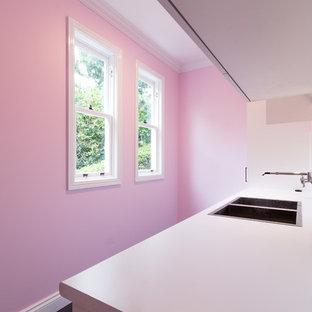 Idées déco pour une buanderie moderne avec un mur rose et un sol gris.