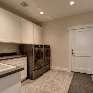 Foto di una grande sala lavanderia stile americano con lavello da incasso, ante in stile shaker, ante bianche, top in superficie solida, pareti beige, pavimento con piastrelle in ceramica e lavatrice e asciugatrice affiancate