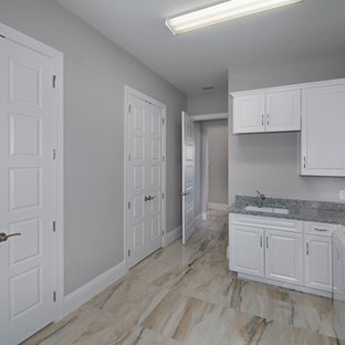 Mid-sized tuscan l-shaped beige floor dedicated laundry room photo in Miami with an undermount sink, raised-panel cabinets, white cabinets and gray walls