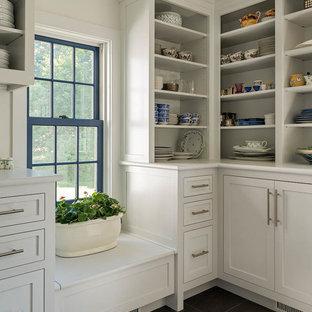 Modelo de cuarto de lavado bohemio, grande, con armarios estilo shaker, puertas de armario blancas, lavadora y secadora juntas, encimera de madera, paredes blancas, suelo de baldosas de cerámica y suelo gris