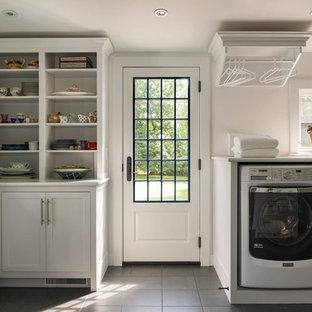 Свежая идея для дизайна: большая п-образная универсальная комната в классическом стиле с фасадами в стиле шейкер, белыми фасадами, белыми стенами, полом из керамической плитки, со стиральной и сушильной машиной рядом и серым полом - отличное фото интерьера