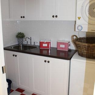 Idéer för att renovera en liten maritim linjär tvättstuga enbart för tvätt, med en nedsänkt diskho, skåp i shakerstil, vita skåp, laminatbänkskiva, vita väggar, en tvättpelare och rött golv