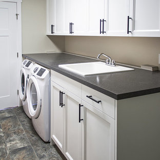 Design ideas for a large arts and crafts galley utility room in Seattle with a drop-in sink, recessed-panel cabinets, white cabinets, laminate benchtops, grey walls, linoleum floors, a side-by-side washer and dryer and grey benchtop.