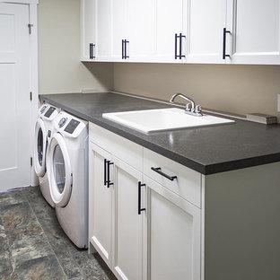 Inredning av ett amerikanskt stort grå parallellt grått grovkök, med en nedsänkt diskho, luckor med infälld panel, vita skåp, laminatbänkskiva, grå väggar, linoleumgolv och en tvättmaskin och torktumlare bredvid varandra