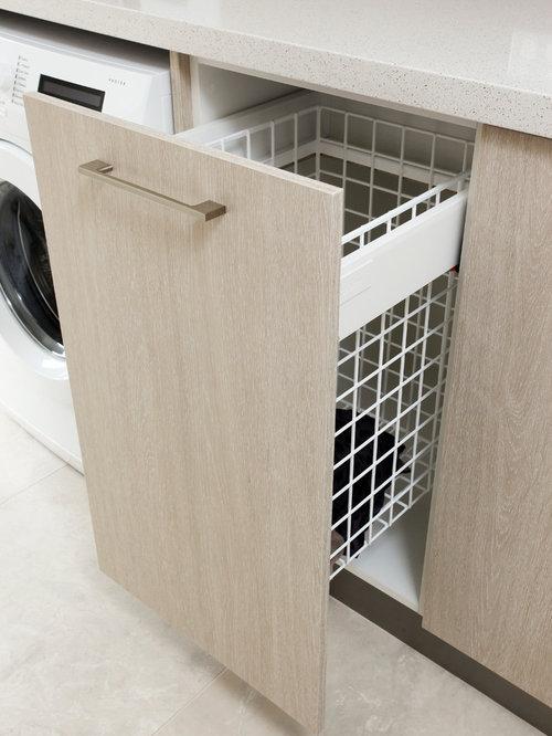 Buanderie moderne avec des portes de placard en bois clair ...