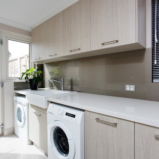 Photo of a modern single-wall laundry room in Perth with a farmhouse sink, flat-panel cabinets, quartz benchtops, light wood cabinets, white benchtop, a side-by-side washer and dryer, ceramic floors and grey floor.