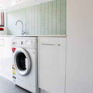Idee per una piccola sala lavanderia minimalista con lavello da incasso, ante lisce, ante bianche, top in quarzo composito, pareti verdi, pavimento in gres porcellanato, lavasciuga, pavimento grigio e top bianco