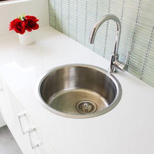 Foto di una piccola sala lavanderia minimalista con lavello da incasso, ante lisce, ante bianche, top in quarzo composito, pareti verdi, pavimento in gres porcellanato, lavasciuga, pavimento grigio e top bianco