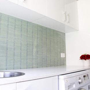 Esempio di una piccola sala lavanderia moderna con lavello da incasso, ante lisce, ante bianche, top in quarzo composito, pareti verdi, pavimento in gres porcellanato, lavasciuga, pavimento grigio e top bianco