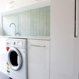 Foto di una piccola sala lavanderia moderna con lavello da incasso, ante lisce, ante bianche, top in quarzo composito, pareti verdi, pavimento in gres porcellanato, lavasciuga, pavimento grigio e top bianco