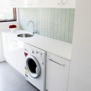 Esempio di una piccola sala lavanderia minimalista con lavello da incasso, ante lisce, ante bianche, top in quarzo composito, pareti verdi, pavimento in gres porcellanato, lavasciuga, pavimento grigio e top bianco