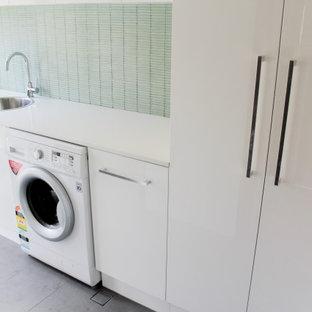 Ispirazione per una piccola sala lavanderia minimalista con lavello da incasso, ante lisce, ante bianche, top in quarzo composito, pareti verdi, pavimento in gres porcellanato, lavasciuga, pavimento grigio e top bianco