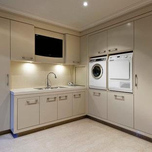Idéer för en modern tvättstuga, med släta luckor, beige skåp, beige väggar, en tvättmaskin och torktumlare bredvid varandra och beiget golv