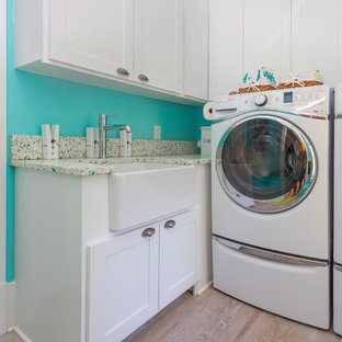 Example of a mid-sized coastal galley light wood floor and beige floor laundry room design in Charleston with a farmhouse sink, raised-panel cabinets, white cabinets, recycled glass countertops, blue walls, a side-by-side washer/dryer and multicolored countertops
