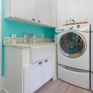 Bild på en mellanstor maritim flerfärgade parallell flerfärgat tvättstuga, med en rustik diskho, luckor med upphöjd panel, vita skåp, bänkskiva i återvunnet glas, blå väggar, ljust trägolv, en tvättmaskin och torktumlare bredvid varandra och beiget golv