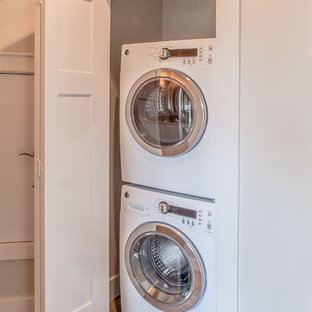 Laundry closet - small transitional linoleum floor laundry closet idea in Portland with white walls and a stacked washer/dryer