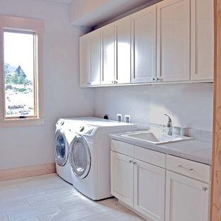 Exempel på ett stort klassiskt grå linjärt grått grovkök, med en nedsänkt diskho, skåp i shakerstil, vita skåp, kaklad bänkskiva, grå väggar, klinkergolv i porslin och en tvättmaskin och torktumlare bredvid varandra