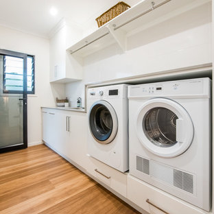Inspiration for a mid-sized contemporary single-wall vinyl floor dedicated laundry room remodel in Other with a single-bowl sink, flat-panel cabinets, white cabinets, granite countertops, white backsplash, ceramic backsplash, white walls, a side-by-side washer/dryer and gray countertops