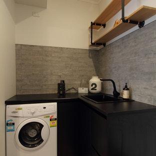 Idee per una piccola sala lavanderia industriale con lavello a vasca singola, ante nere, top in laminato, pareti grigie, pavimento in laminato, lavatrice e asciugatrice a colonna e ante lisce
