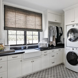 Inspiration for a timeless l-shaped multicolored floor dedicated laundry room remodel in Phoenix with a farmhouse sink, shaker cabinets, white cabinets and black countertops
