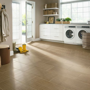 Ispirazione per una grande sala lavanderia chic con ante bianche, pavimento in laminato, lavatrice e asciugatrice affiancate, ante lisce, top in cemento, pareti beige, pavimento beige e top grigio