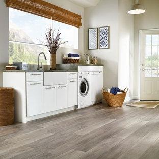 Bild på en stor lantlig linjär tvättstuga enbart för tvätt, med en rustik diskho, släta luckor, vita skåp, vita väggar, vinylgolv och en tvättmaskin och torktumlare bredvid varandra
