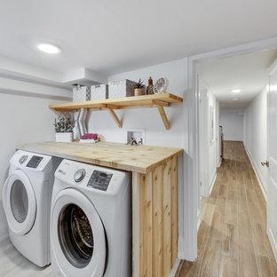 Esempio di una sala lavanderia scandinava di medie dimensioni con nessun'anta, ante in legno chiaro, top in legno, pareti bianche, lavatrice e asciugatrice affiancate, pavimento con piastrelle in ceramica e pavimento grigio