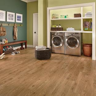 Inredning av en klassisk stor linjär liten tvättstuga, med öppna hyllor, vita skåp, bänkskiva i koppar, gröna väggar, mellanmörkt trägolv, en tvättmaskin och torktumlare bredvid varandra och brunt golv