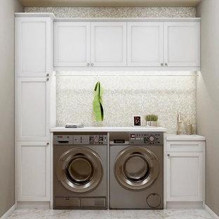 Klassisk inredning av en liten tvättstuga, med en undermonterad diskho, vita skåp, grå väggar, marmorgolv och vitt golv