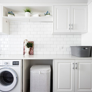 Mid-sized traditional single-wall dedicated laundry room in Brisbane with white cabinets, quartz benchtops, white walls, white benchtop, a drop-in sink and raised-panel cabinets.